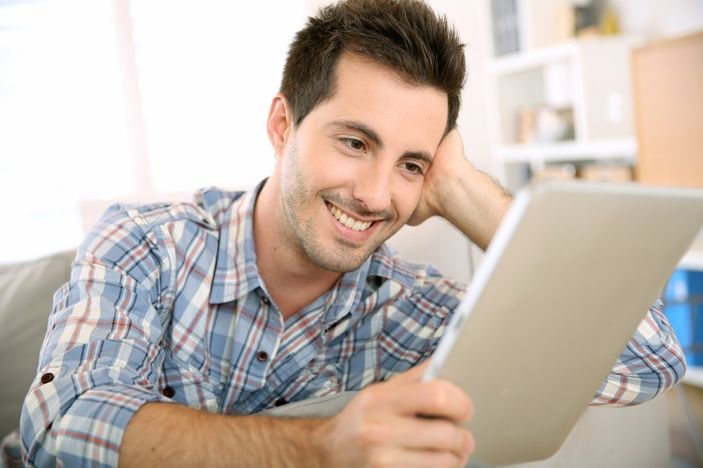 Cheerful handsome guy using tablet to read mail